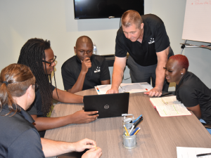 CEO Rodney McLeod (second from right) gives instructions to the MIS team on DNS architecture
